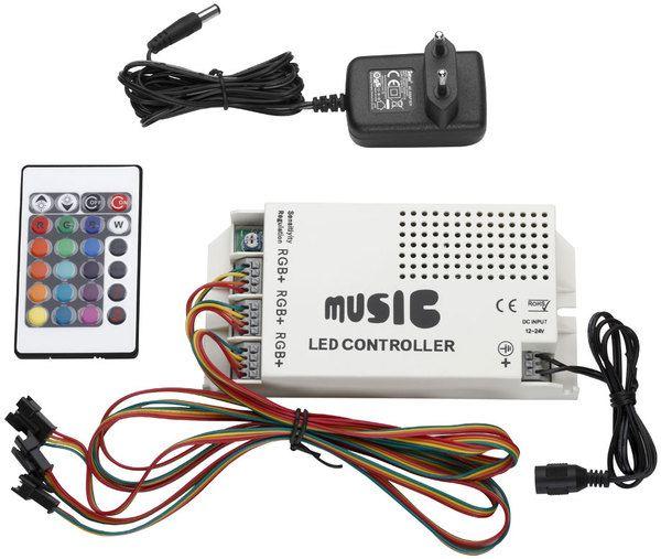 Eine etwa DIN A5 große, weiße Plastikbox mit mehreren Ein- und Ausgängen für Kabel. Es gibt auch einen integrierten Lautsprecher, eine kleine Fernbedienung mit bunten Knöpfen und ein einzelnes Netzteil.