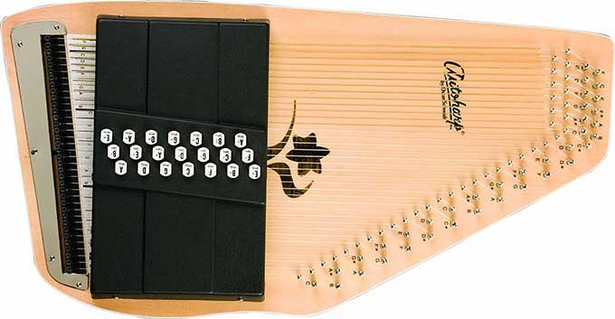 Ein flaches Holzinstrument, etwa so groß wie eine Geige. Die Oberfläche hat viele Saiten gespannt und auf dem unteren Bereich zusätzlich einen schwarzen Aufsatz. Hier gibt es kleine weiße Knöpfe mit Notenbezeichnungen drauf
