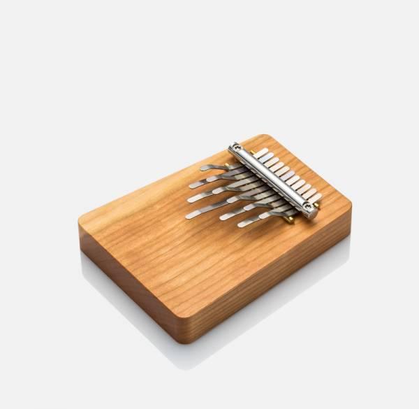 Ein kleiner Holzblock, der unterschiedlich hohe und unterschiedlich kurze, platte Metallstäbchen hat. Befestigt sind die an einer Art kleinen Tastatur, die ebenfalls aus Metall besteht.