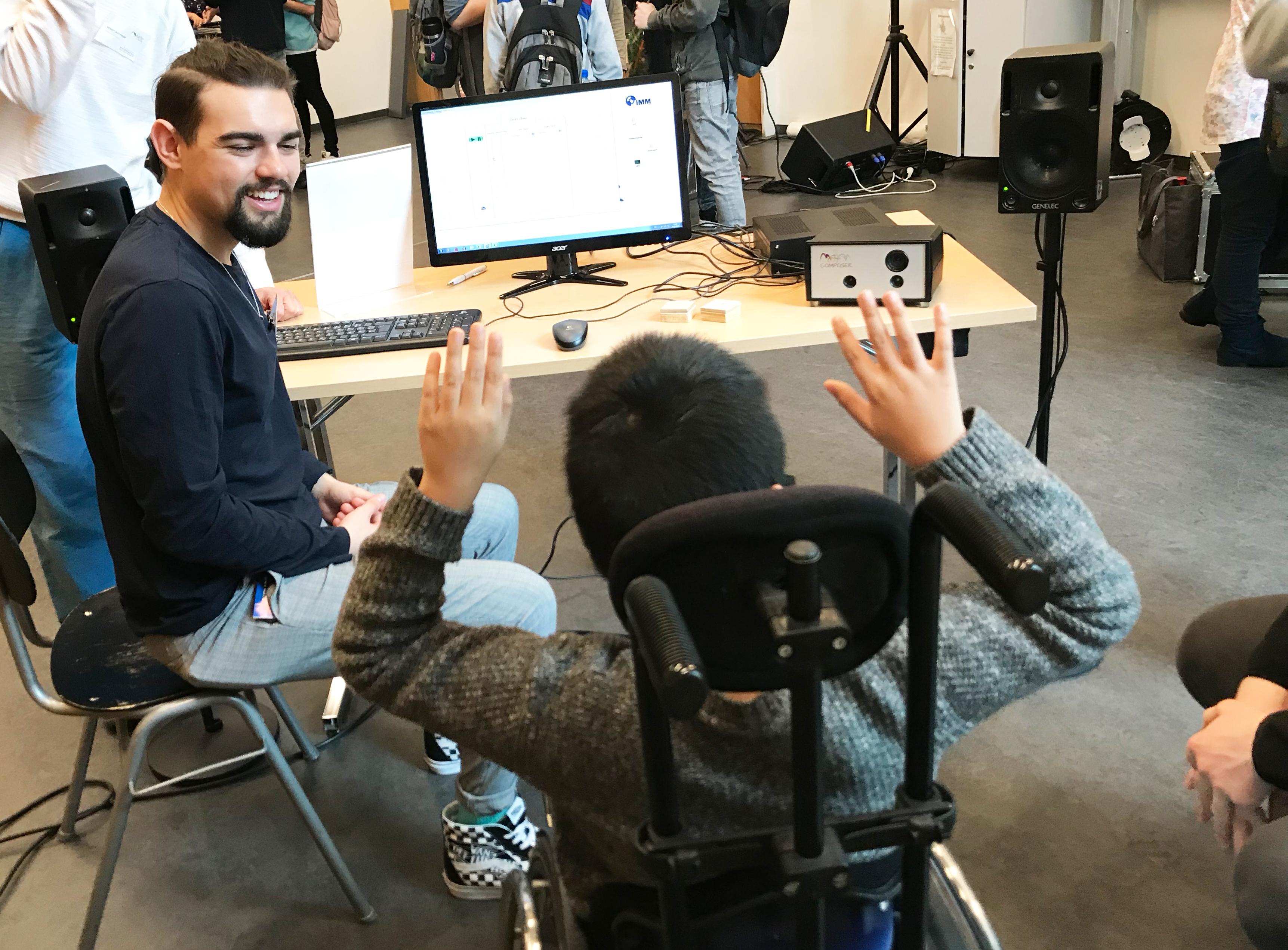 Links sitzt ein Mann auf einem Stuhl und in der Mitte ein junger Mann im Rollstuhl mit den Händen in der Luft. Beide sitzen vor einem Schreibtisch mit einem Computer.