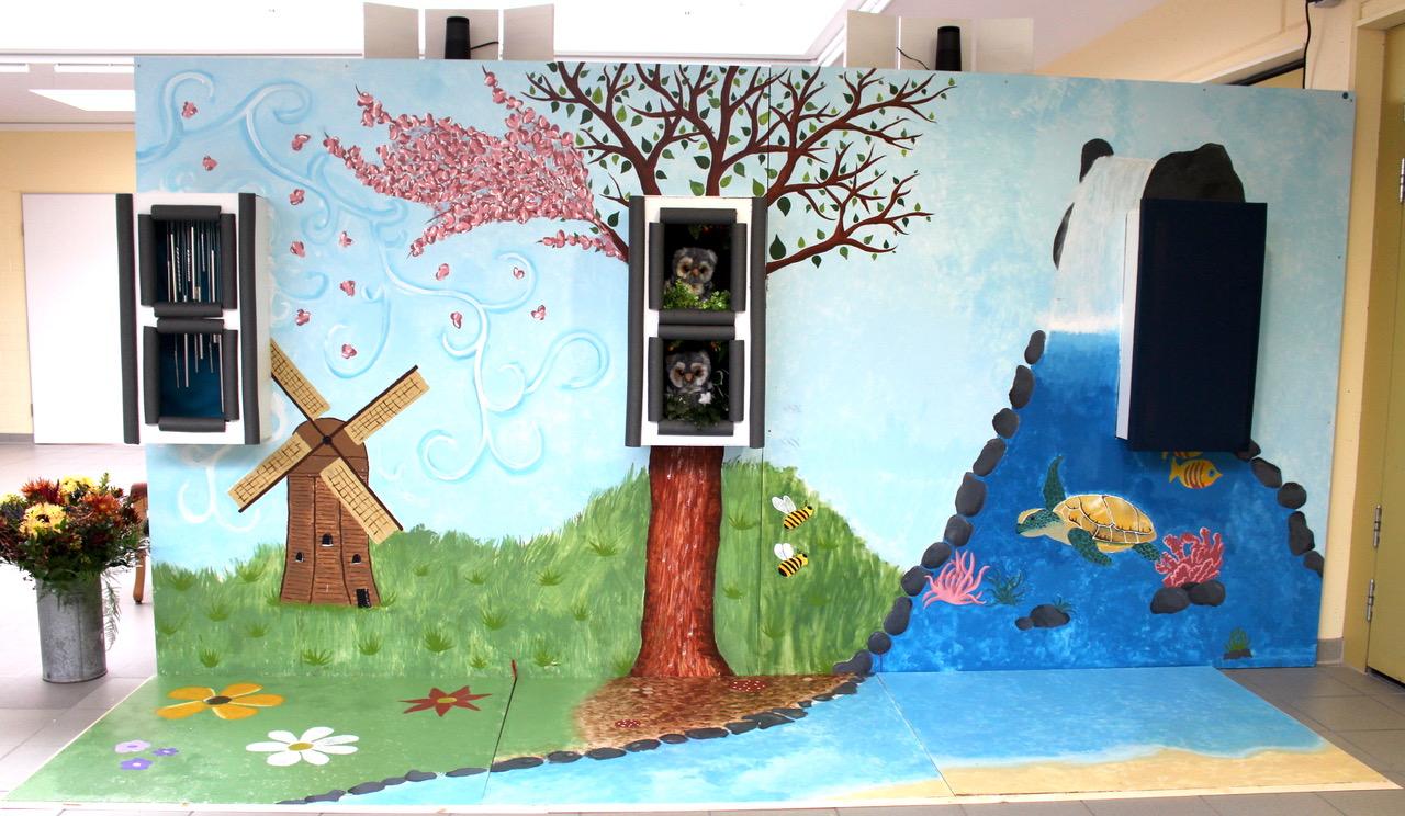Die Klangwand ist bemalt. Auf der linken Seite sind eine Windmühle und Gras sowie zwei in der Wand versenkten Regalöffnungen mit Metallstangen drin. In der Mitte steht ein Baum, in den ebenfalls zwei Regalöffnungen eingelassen sind, in denen zwei Plüscheulen sitzen. Im Vordergrund und rechts ist Wasser, eine Wasserschildkröte und ein großer Lautsprecher.
