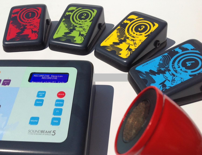 Ein kleiner elektronischer Kasten mit winzigem Display. Auf mehreren Knöpfen kann man Lautstärke usw. regeln. Drumherum stehen kleine Pedalen mit verschiedenen Farben und Zahlen von Eins bis Vier und ein Lautsprecher.