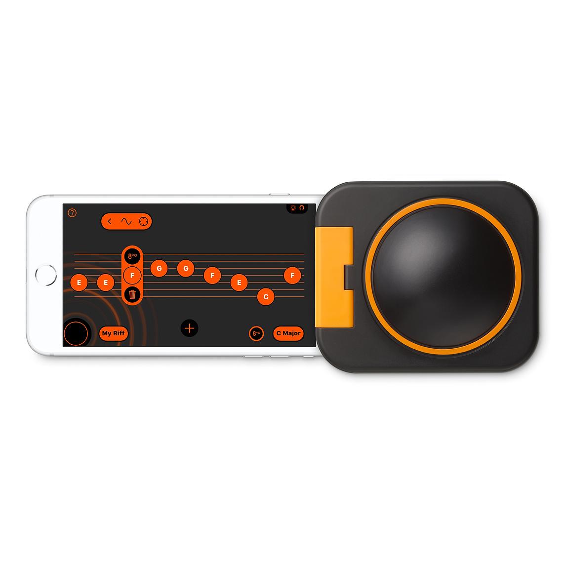 Ein weißes Smartphone zeigt Notenlinien und Noten. Es steckt in einem dunklen Plastikwürfel, der oben einen runden Knopf hat.