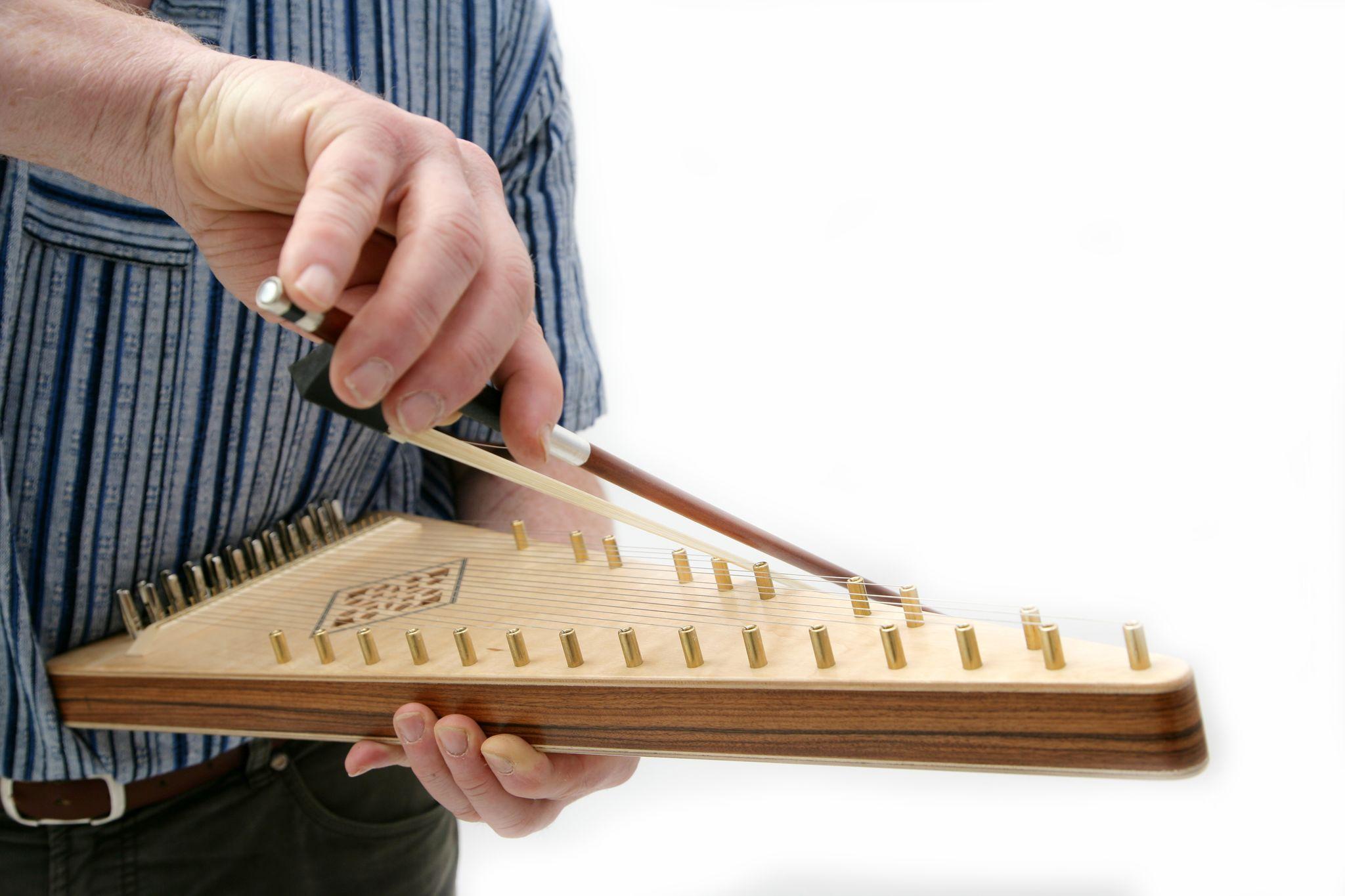 Mit einem Geigenbogen streicht jemand über über die Saiten von einem kleinen dreieckigen, dreidimensionalen Instrument aus Holz. Es hat viele Saiten von unten nach oben über den Korpus gespannt, die von kurzen Metallstiften umringt sind.