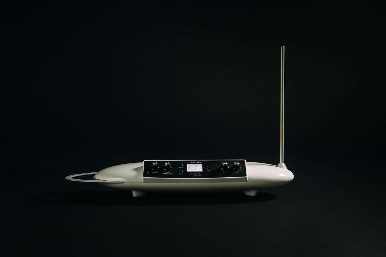 Eine ovale, runde Plastikbox, die auf zwei Füßchen steht und auf einer Seite eine Schaltoberfläche hat. Rechts außen befindet sich eine Antenne.